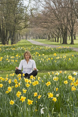 woman meditating in a park amongst spring daffodils