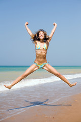 Attractive girl jumping on the beach
