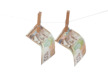 One hundred dollar bills hanging from a clothes line