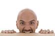 Mann mit Glatze beißt in Tischkante