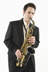 Mid adult man stands in suit playing the saxophone
