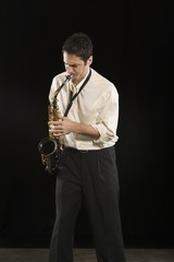 Mid adult man stands in shirt playing the saxophone