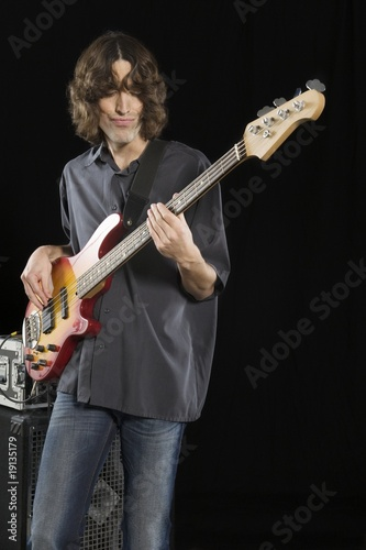 Mid adult man stands playing an electric guitar
