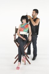 Hair stylists adjusts young models hair