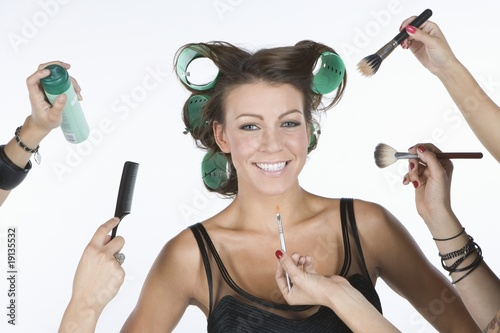 Woman in rollers , with cosmetics products on hand