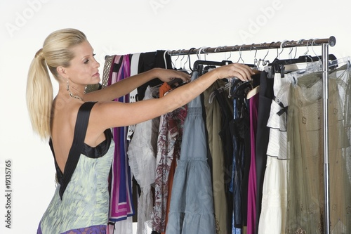 Woman chooses from a selection of items on a clothes rail