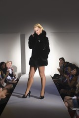 Woman in short black furcoat stands on fashion catwalk
