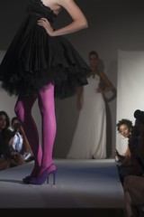 Low section of woman in pink tights and party dress on fashion catwalk