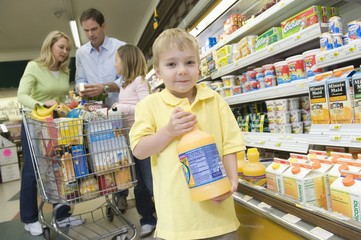 Young boy holds orange juice while family shop in supermarket