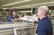 Supermarket employee hands product to customer in supermarket delicatessen