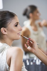 Profile of woman sitting in makeup, lip gloss application