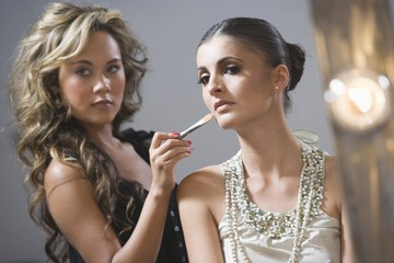 Make up artist applying foundation to fashion model