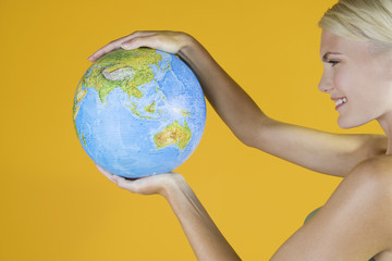 A Young Woman Holding A Globe