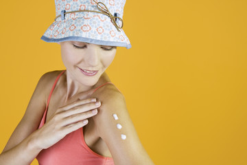 A Young Woman Rubbing Suntan Cream Into Her Arm