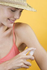 A Young Woman Spraying Suntan Lotion On Her Arm