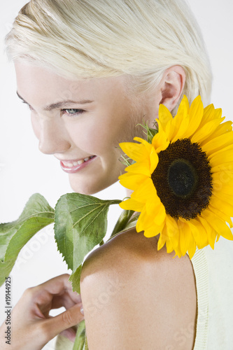 A Young Woman With A Sunflower Resting On Her Shoulder