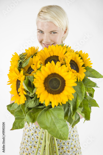 A Young Woman Holding A Bunch Of Sunflowers
