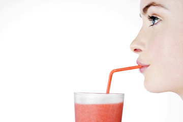 A Young Woman Drinking A Fruit Drink Through A Straw