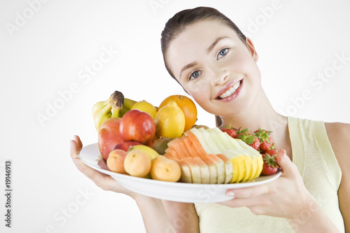 A Young Woman Holding A Bowl Of Fruit