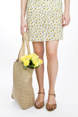 A Young Woman Carrying A Bunch Of Yellow Roses In A Shopping Bag