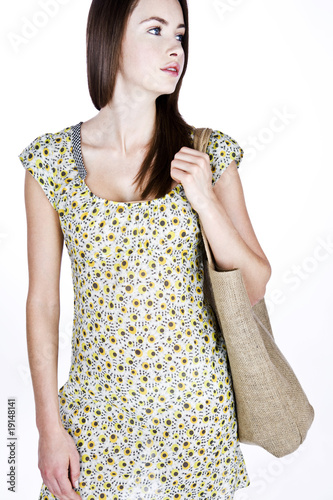 A Young Woman Carrying A Shopping Bag Over Her Shoulder