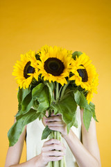 A Young Woman Behind A Bunch Of Sunflowers