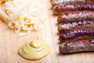 Bratwurst, Senf und Sauerkraut auf einer Holztafel