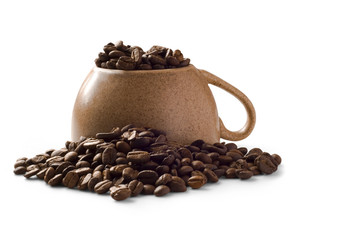 Overturned brown isolated cup with cofee beans over it