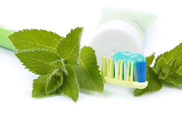 Toothbrush, toothpaste and fresh leaves of mint