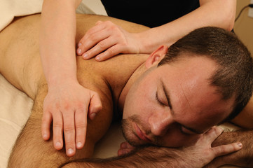 Massaging Shoulder and Back of Man at Day Spa