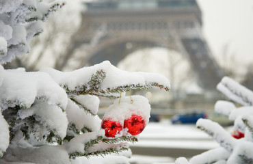 Rare snowy day in Paris. Decorated Christmas tree and the Eiffel