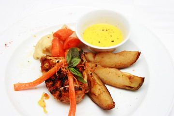 Grilled chicken with potato wedges isolated