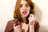 jeune femme avale une pillule en tirant sur sa chemise