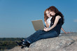 two girls with laptop working on a rock
