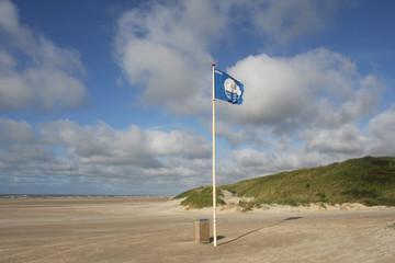 Blaue Flagge am breiten Strand
