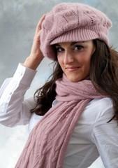 Eine junge Frau posiert mit rosa Schal und  Kappe