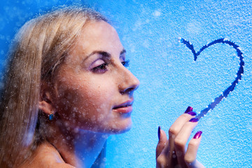 Beautiful blond woman draws heart on the frozen glass