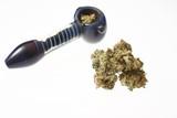 Medical marijuana next to a glass pipe. poster