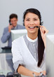 Laughing asian businesswoman with headset on at a computer