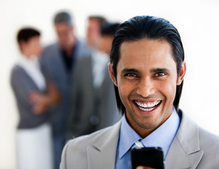 Cheerful ethnic businessman sending a text