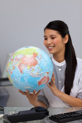 Smiling asian businesswoman looking at a globe