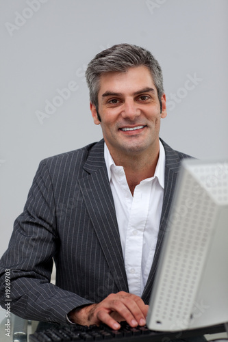 Self-assured male executive working at a computer