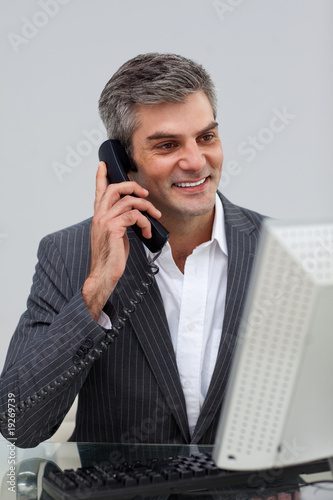Positive male executive talking on phone