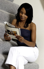 African American woman relaxing reading magazine