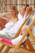 Happy family with little girl reclining on chaise lounges