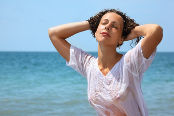beautiful woman in wet clothes on seacoast, closed eyes