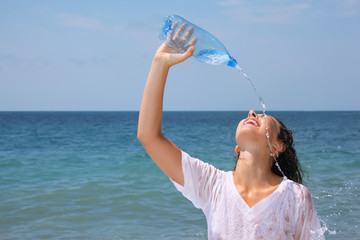 beautiful woman watering from bottle on seacoast, closed eyes