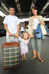 Happy family with girl at railway station, focus on daughter