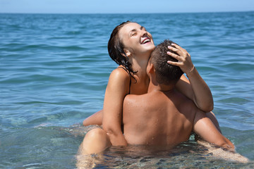young hot woman sitting astride man in sea near coast, closed ey
