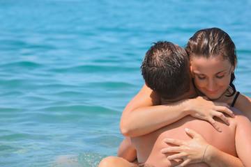 young hot woman sitting astride man in sea near coast